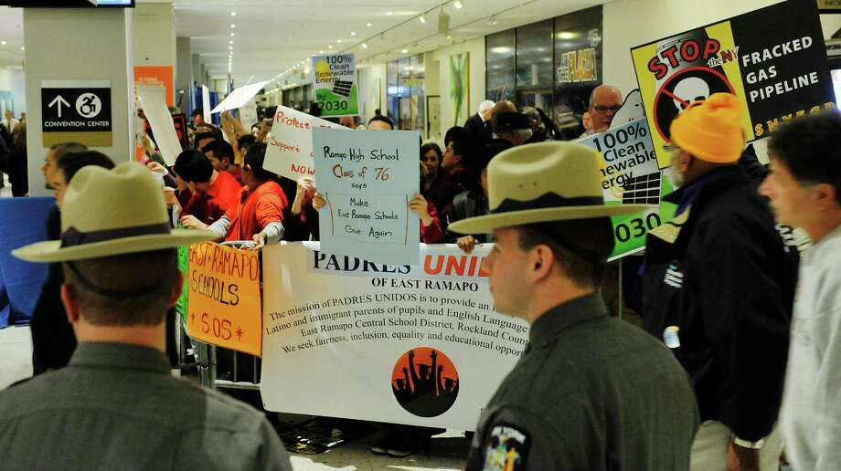 Protestors from various groups hold signs behind a barricade on the Empire State Plaza concourse outside of where Governor Andrew Cuomo was delivering his State of the State address on Wednesday, Jan. 13, 2016, in Albany, N.Y.   (Paul Buckowski / Times Union)