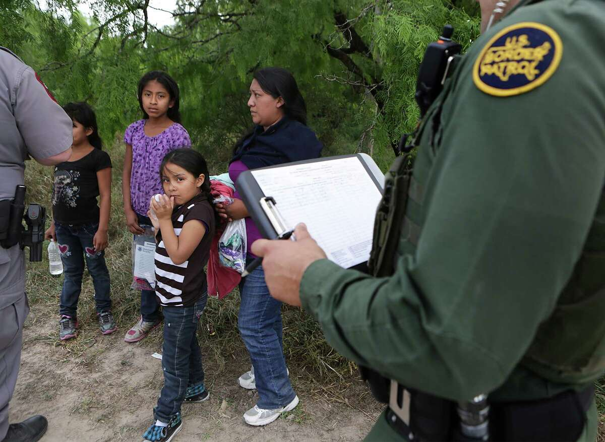 A family unit and unaccompanied minors encountered by Border Patrol Agents and Texas Game Wardens, wait as paper work is filled out. Immigrants from Central America still coming across the Rio Grande in search of a better, safer life, away from the violence and poverty in their own countries. Wednesday, April 8, 2015.