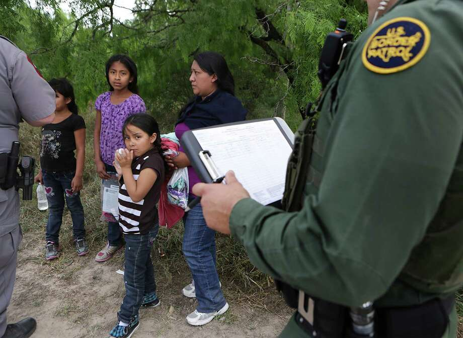 A family unit and unaccompanied minors encountered by Border Patrol Agents and Texas Game Wardens, wait as paper work is filled out.  Immigrants from Central America still coming across the Rio Grande in search of a better, safer life, away from the violence and poverty in their own countries.   Wednesday, April 8, 2015. Photo: Bob Owen, Staff / San Antonio Express-News / © 2015 San Antonio Express-News