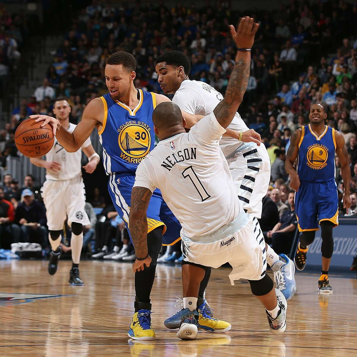Stephen Curry #30 of the Golden State Warriors tries to retain control of the ball against the defense of Jameer Nelson #1 and Gary Harris #14 of the Denver Nuggets at Pepsi Center on January 13, 2016 in Denver, Colorado.