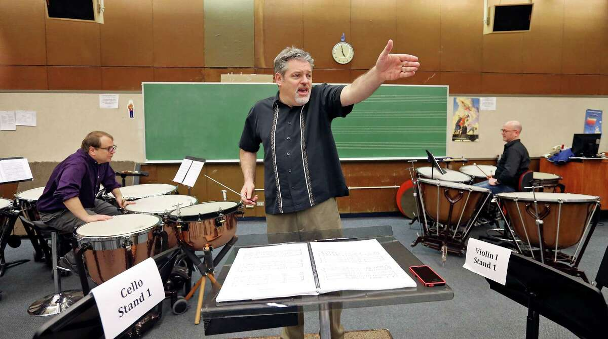 YOSA Music Director Troy Peters leads timpanists Peter Flamm (left) and Peter Wilson (right) and YOSA members in a rehearsal for YOSA's Danzas de las Américas part of the S.A. Symphony's Las Américas Festival.