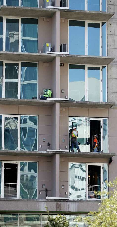Workers install windows of the Skyhouse, a pair of high-rise residential towers downtown at 1625 Main. One is open and the second is under construction on Tuesday, Jan. 12, 2016, in Houston. ( Karen Warren / Houston Chronicle ) Photo: Karen Warren, Nancy Sarnoff / © 2015  Houston Chronicle
