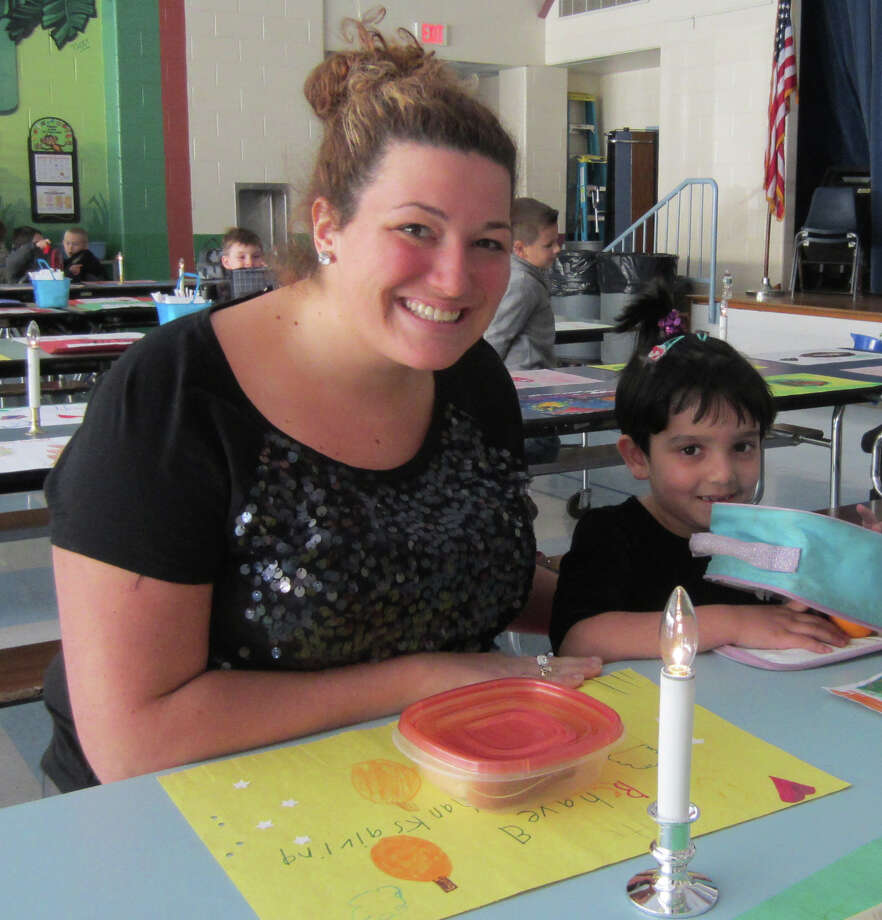 Kindergarten teacher Katie Carr joins student Ayesha Hussain, one of first few guests to arrive at Hill and Plain Elementary School's recent Friendship Luncheon in New Milford. Photo: Courtesy Of Hill And Plain Elementary School / The News-Times Contributed