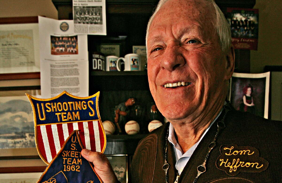 Displaying patches from U.S. Shooting Team and U.S. International Skeet Team, Tom Heffron wears the bronze individual medal and holds the gold team medal he won by beating the undefeated Soviet Union's team in 1962 at the height of the Cold War.