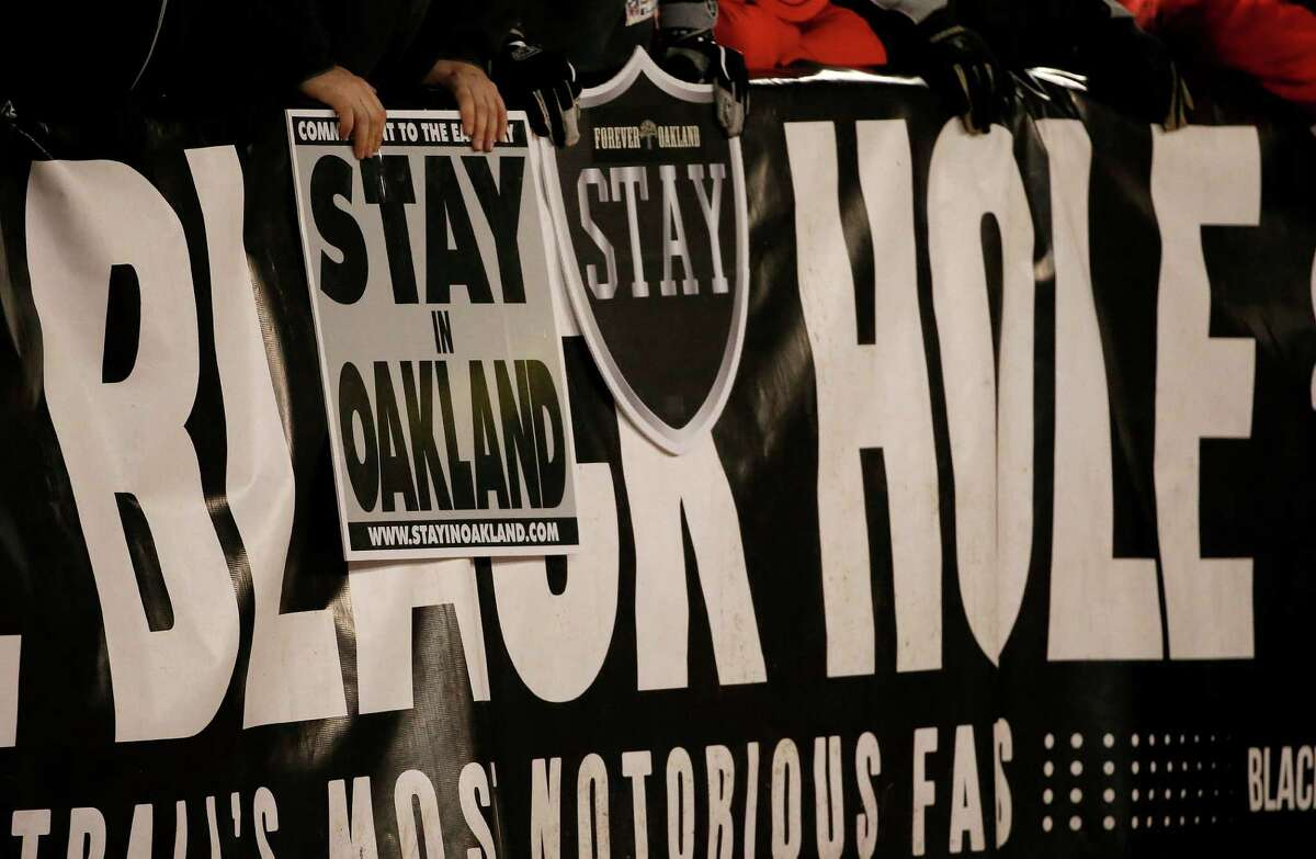 Fans hold up sign for the Oakland Raiders to remain in Oakland during the first half of an NFL football game between the Oakland Raiders and the San Diego Chargers in Oakland, Calif., on Dec. 24, 2015.