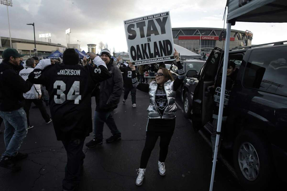 """Felicia Gonzales holds a """"Stay in Oakland"""" sign as other fans pass by in the parking lot before the Oakland Raiders played the San Diego Chargers at O.Co Coliseum on Dec. 24, 2015."""