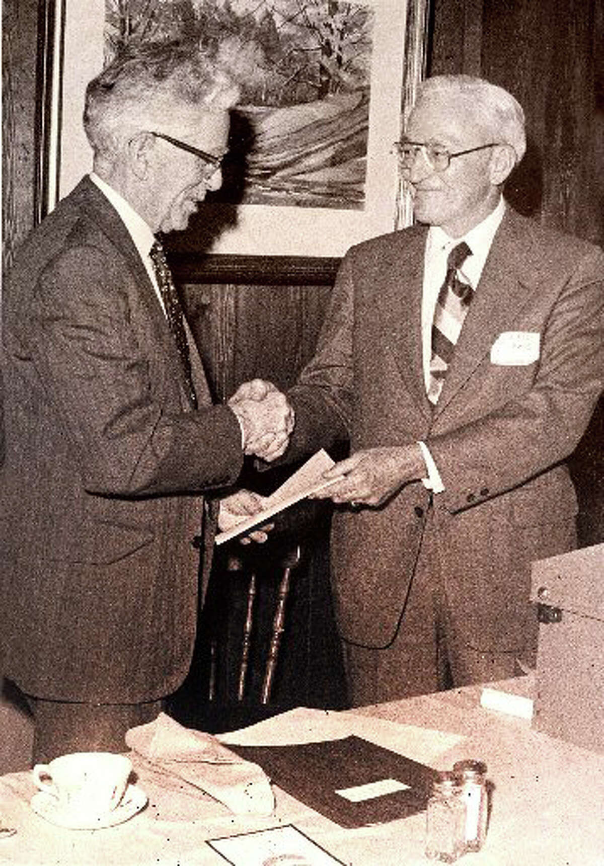 First Selectman John Sullivan receives the deed for open space given to the town by GE, from GE's Robert Lewis. The 1974 acquisition became known as the Cascades at the Lake Mohegan open space.