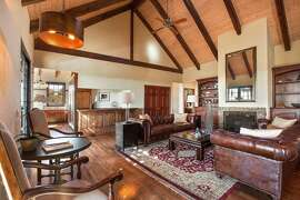 A voluminous great room includes built-ins, a vaulted, beamed ceiling and access to a view balcony.