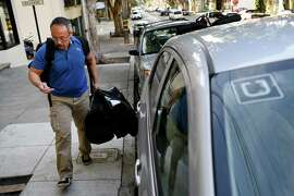 Uber driver Lyndon Bell, of Vallejo, loads bags of food into his car in San Francisco last year. The California Public Utilities Commission ruled today that an Uber subsidiary must pay a $7.6 million fine to for failing to hand over required information.