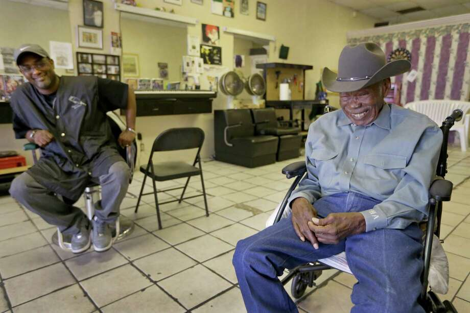 Barber Charles Jones (left) shares a laugh with Paul Cleveland, a member of the National Cowboys of Color Hall of Fame at Mr. C's Barber Shop in Humble. Photo: Melissa Phillip, Houston Chronicle / © 2016 Houston Chronicle