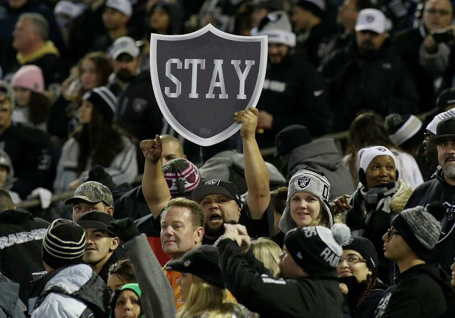 Fans hold up a sign for the Raiders to stay in Oakland before the home game against San Diego Chargers on Dec. 24, 2015. Photo: Jeff Chiu /Associated Press / AP