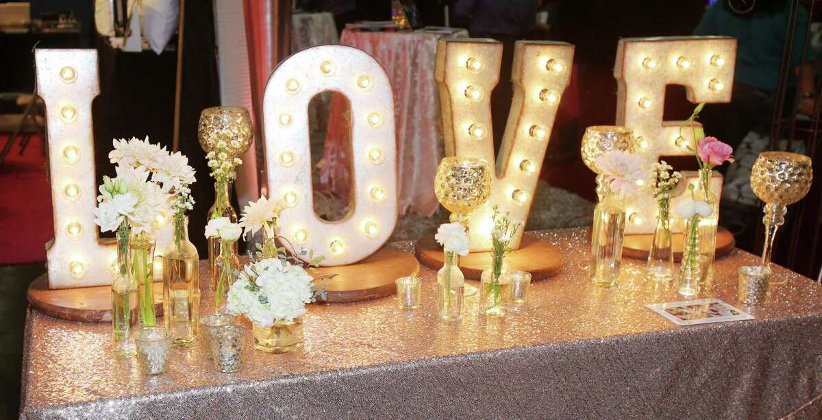 """Marquee letters: Rustic chic décor remains one of the most in-demand wedding motifs as illustrated by The Bloom Room's aptly designed display; brides continuously swarmed the tented stall to photograph the floral studio's vintage """"L-O-V-E"""" marquee sign."""