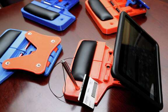 Several prototypes of swiveling iPad stands that will hold an electronic poll book at polling sites are shown in the office of Stan Stanart, Harris County County Clerk, at 201 Caroline Wednesday, Jan. 13, 2016, in Houston. The iPad can be used to read the barcode on a driver's  license.