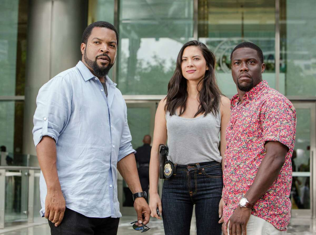 """This photo provided by Universal Pictures shows, Ice Cube, from left, as James Payton, Olivia Munn as Maya Cruz, and Kevin Hart as Ben Barber in a scene from the film, """"Ride Along 2."""" The movie opens in U.S. theaters on Jan. 15, 2016. (Quantrell D. Colbert/Universal Pictures via AP)"""