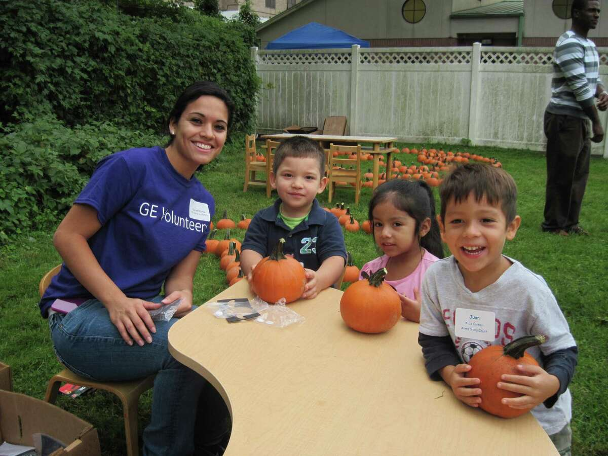 In this file photo, a GE Capital Real Estate volunteer decorates pumpkins with children enrolled in the Family Center's Early Care and Education and Head Start preschools.