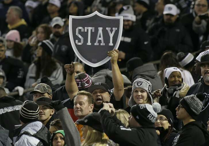 Fans hold up a sign for the Oakland Raiders to stay in Oakland before an NFL football game between the Oakland Raiders and the San Diego Chargers in Oakland, Calif., Thursday, Dec. 24, 2015. (AP Photo/Jeff Chiu)