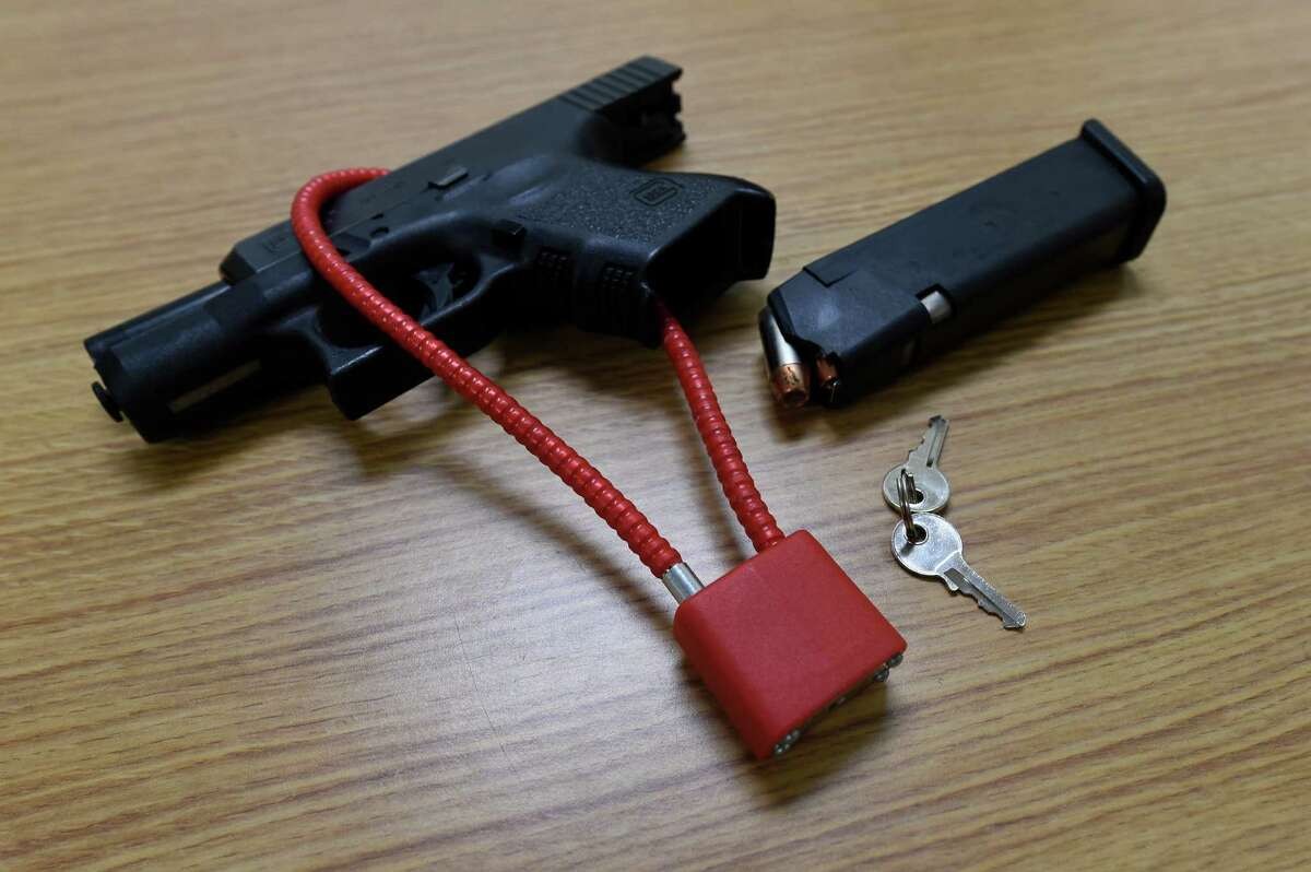 A hand gun is locked up for display Thursday, Jan. 14, 2016, at the Albany Police Headquarters in Albany, N.Y. City police are distributing free gun locks to coincide with the implementation of a new law requiring gun owners to store their firearms securely. (Skip Dickstein/Times Union)