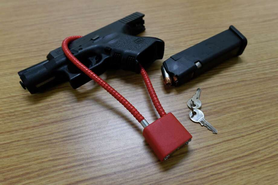 A hand gun is locked up for display Thursday, Jan. 14, 2016, at the Albany Police Headquarters in Albany, N.Y. City police are distributing free gun locks to coincide with the implementation of a new law requiring gun owners to store their firearms securely.  (Skip Dickstein/Times Union) Photo: SKIP DICKSTEIN / 10035008A