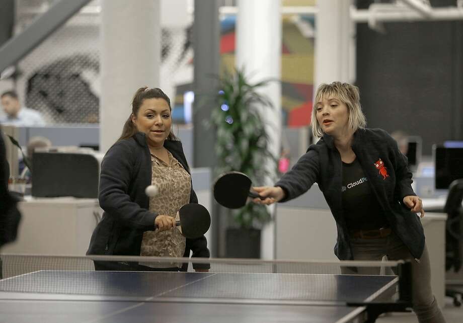 BDR Jacquie Frink (left) and office manager Kelsey Jones (right) play ping pong with ADR Kevin Summer (not seen) in the basement offices of CloudPassage in San Francisco, California, on Wednesday,  January 13, 2015. Photo: Liz Hafalia, The Chronicle