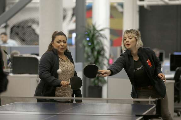 BDR Jacquie Frink (left) and office manager Kelsey Jones (right) play ping pong with ADR Kevin Summer (not seen) in the basement offices of CloudPassage in San Francisco, California, on Wednesday,  January 13, 2015.