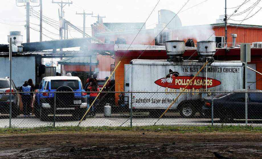 Smoke emanates from a portable cook stand as well as from an affixed building at Pollos Asados Los Nortenos restaurant on Rigsby Avenue on Thursday, Jan. 14, 2016. Some neighbors have complained about the large quantities of smoke that spills into the nearby neighborhood which they believe are causing respiratory issues for people in the area. (Kin Man Hui/San Antonio Express-News) Photo: Kin Man Hui, Staff / San Antonio Express-News / ©2016 San Antonio Express-News