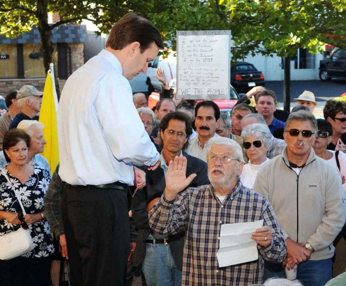 Congressman Chris Murphy, at an outdoor town hall meeting held at the Town Green, in Danbury, CT, on Wednesday, Sept. 2, 2009. Murphy listens to Bob Anger, of Redding, CT, read a statement regarding helathcare reform.