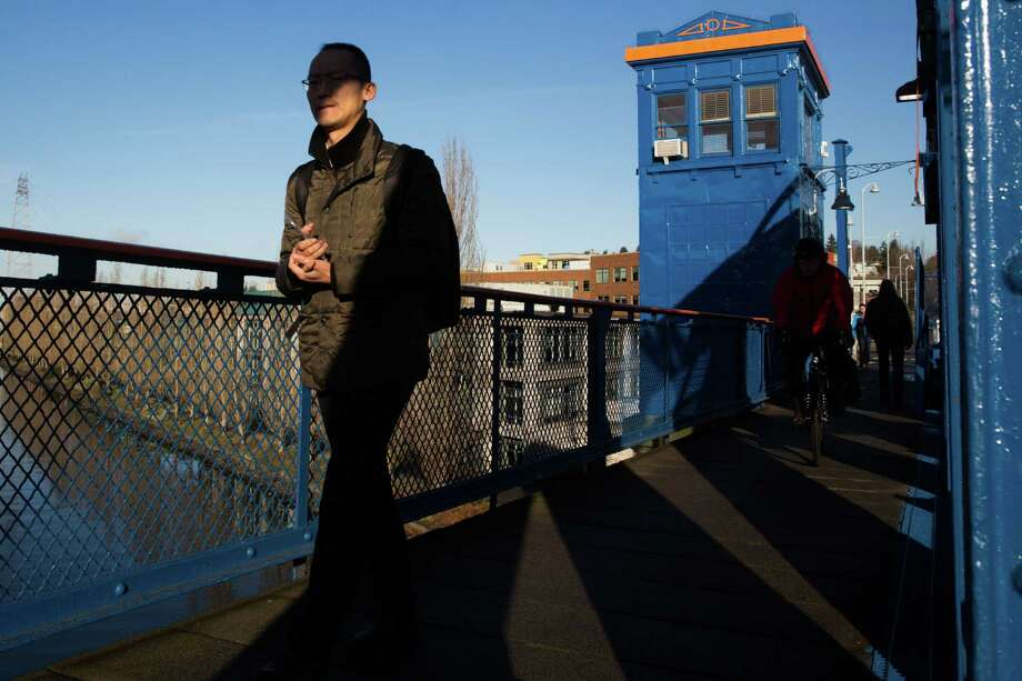 Walkers stroll across the Fremont Bridge with the northwest tower, used as an artist's studio, seen in the background, on Thursday, Jan. 14, 2016. Photo: Grant Hindsley, SEATTLEPI.COM / SEATTLEPI.COM