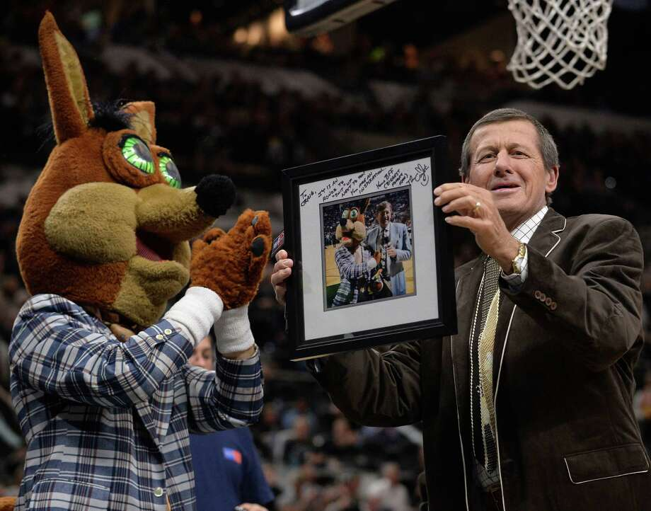 Television sports commentator Craig Sager, right, is presented with a framed photo print by the San Antonio Spurs Coyote during the first half of the Spurs' NBA basketball game against the Cleveland Cavaliers, Thursday, Jan. 14, 2016, in San Antonio. (AP Photo/Darren Abate) Photo: Darren Abate, Associated Press / FR115 AP