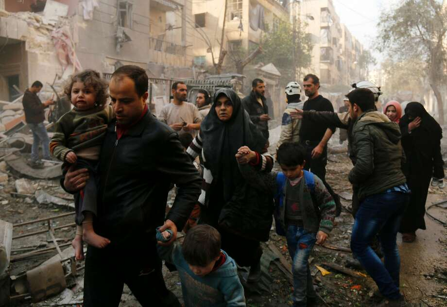 Syrians make their way through debris as they leave for a safer place following air strikes in the rebel-controlled side of the northern city of Aleppo on January 13, 2016. On January 12, 2016, suspected Russian strikes killed 57 civilians, including children and paramedics, in Idlib province, adjacent to Latakia, and in Aleppo, Syrian Observatory for Human Rights said. Photo: Karam Al-masri, AFP / Getty Images