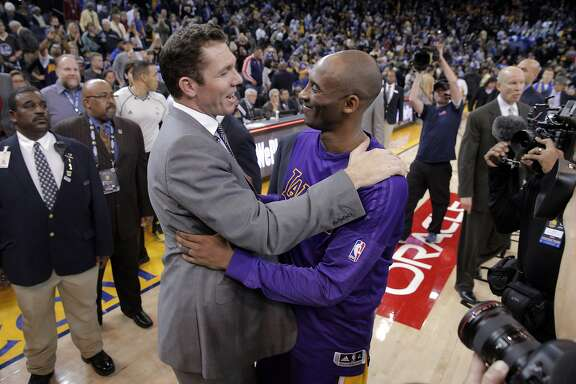 Kobe Bryant (24) hugs Luke Walton, the Warriors interim coach and Kobe's former Lakers teammate after the Golden State Warriors played against the Los Angeles Lakers at Oracle Arena in Oakland, Calif., on Thursday, January 14, 2016.