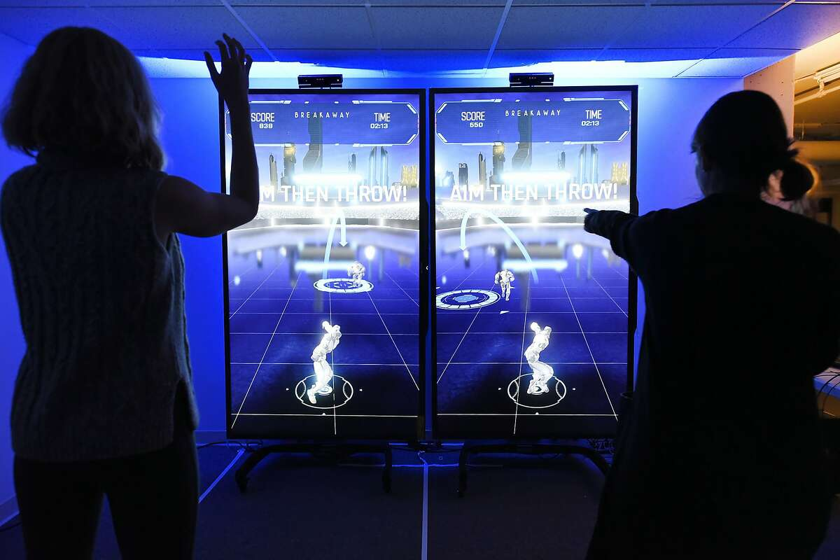 Elaine Cleland, left, and Stephanie Martin of the Super Bowl 50 Host Committee play a motion sensing interactive football game called