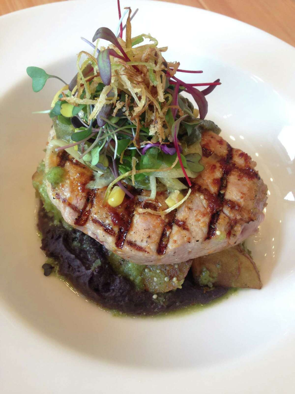 Grilled tuna steak served with refried black beans, potatoes in green sauce and poblano pepper