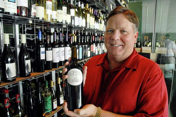 Owner Bill Floyd holds a 2004 Napa Valley Harlon Estate at his restaurant Reef Monday Aug. 25,2008.