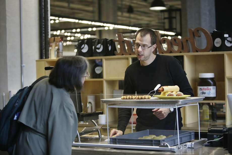 Lukas Bazant, Oui Snack employee, helps a customer at Oui Snack in The Market on Market on Thursday, January 14, 2015 in San Francisco, Calif. Oui Snack started as a temporary pop up and is moving into a permanent space in The Market on Market. Photo: Lea Suzuki, The Chronicle