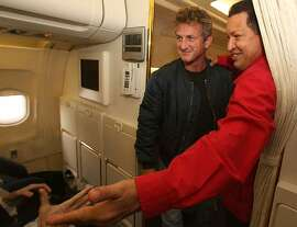 In this photo released by Miraflores Press Office, Venezuela's President Hugo Chavez, right, and the U.S. actor Sean Penn are seen during their flight to Venezuela's Tachira state, Friday, Aug 3, 2007. (AP Photo/Miraflores Press Office)  ** NO SALES ** Ran on: 08-04-2007 Venezuelan President Hugo Chavez (right) and actor Sean Penn greet fellow passengers on their flight to Venezuela's Tachira state on Friday. Penn, who has also visited Iraq and Iran, said he was in the country working as a freelance journalist. &quo;I came here looking for a great country. I found a great country,&quo; Penn said.