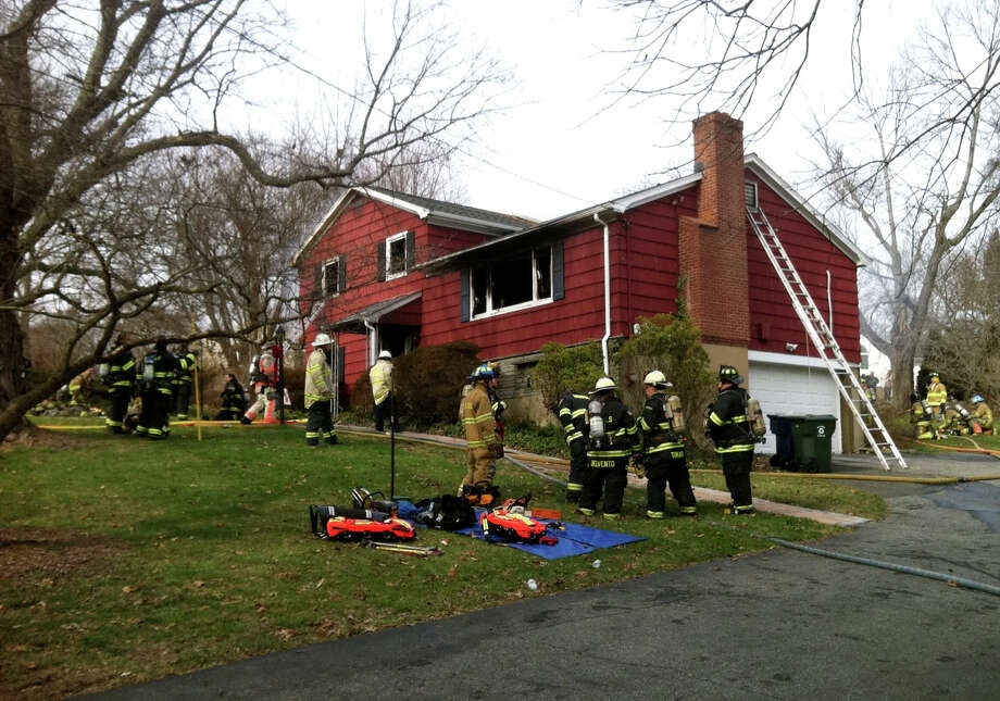 Firefighters on the scene of a house fire at 15 Sunnycrest Rd. in Trumbull, Conn. on Friday, Jan. 15, 2016. Everyone is reported to be out of the building safely. Photo: Ned Gerard, Hearst Connecticut Media / Connecticut Post