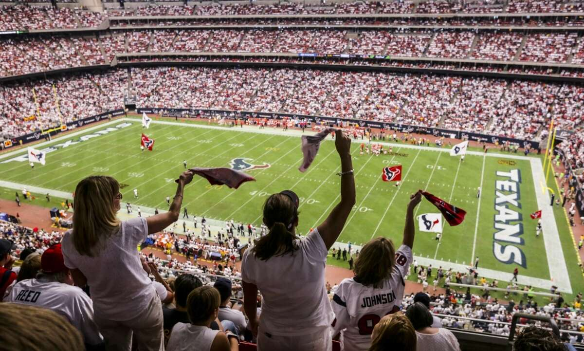 Madonna Pool, left, Shannon Reynold and Lorie Stubbs stand and cheer during a Texans game on Sept. 13, 2015. The Wi-Fi system going up at NRG Stadium will cost in excess of $6 million.