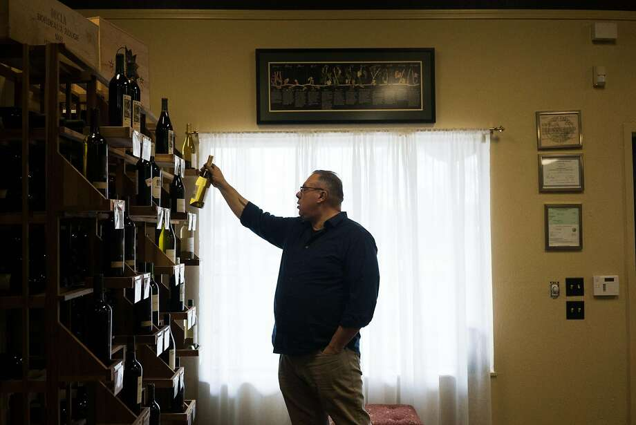 Sommelier and winemaker Thomas Allan takes a wine bottle off the shelf at Amador 360 in Plymouth (Amador County). Photo: James Tensuan
