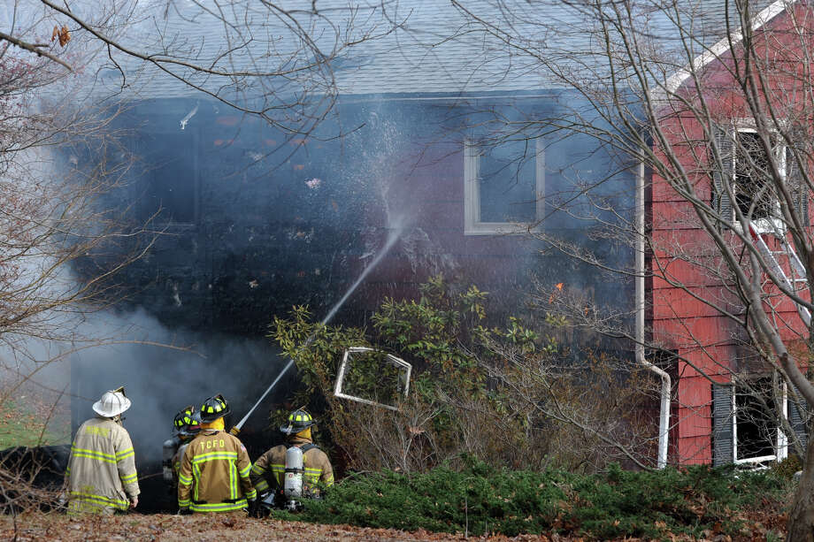 Firefighters on the scene of a house fire at 15 Sunnycrest Rd. in Trumbull, Conn. on Friday, Jan. 15, 2016. Photo: Ned Gerard, Hearst Connecticut Media / Connecticut Post