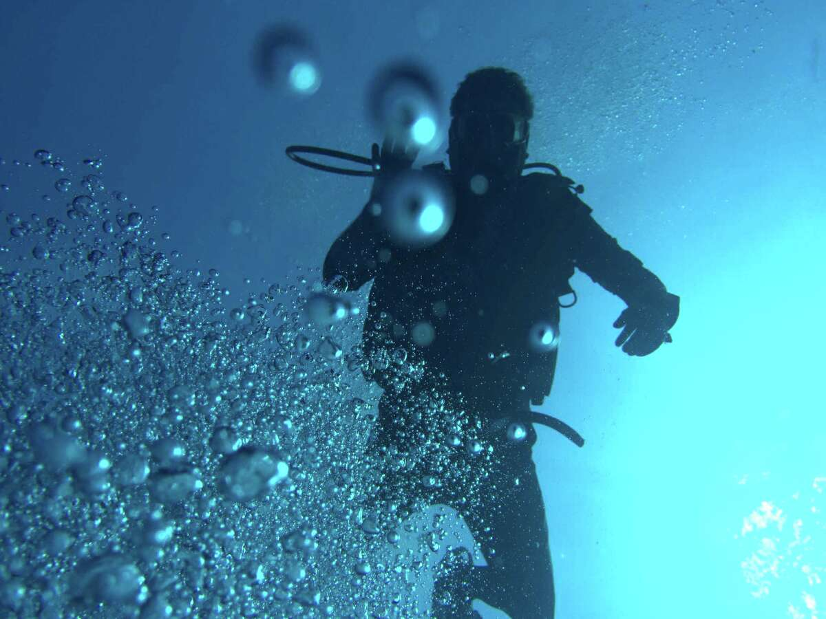 Framed in scuba bubbles, the author, Josh White, waves during a dive.