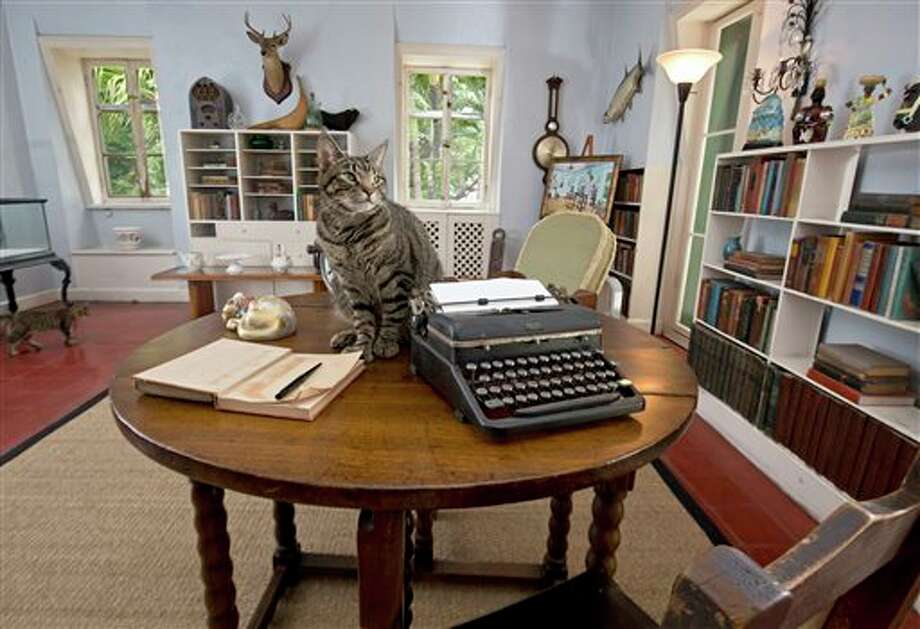 A cat sits on a writing table once used by Ernest Hemingway in the author's studio at the Ernest Hemingway Home & Museum in Key West, Fla. The prize for the winner of the Florida Keys Flash Fiction literary contest is to include the opportunity to spend up to 10 days writing in the study. Hemingway lived in Key West throughout most of the 1930s. Photo: Rob O'Neal /Florida Keys News Bureau Via AP / Florida Keys News Bureau