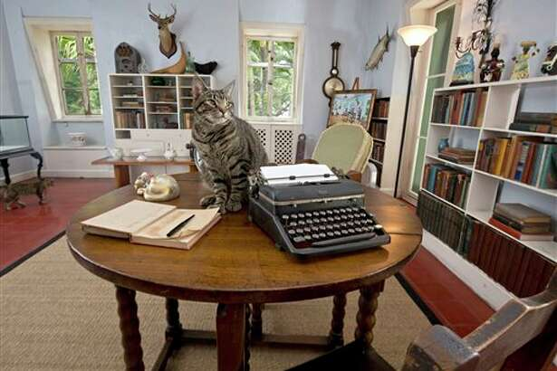 A cat sits on a writing table once used by Ernest Hemingway in the author's studio at the Ernest Hemingway Home & Museum in Key West, Fla. The prize for the winner of the Florida Keys Flash Fiction literary contest is to include the opportunity to spend up to 10 days writing in the study. Hemingway lived in Key West throughout most of the 1930s.