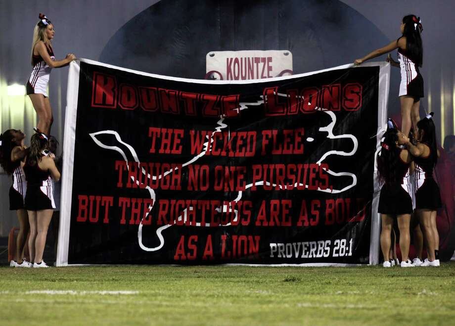 Kountze Lion's cheerleaders hold other members of their squads up to support a a larger banner at Lion's Stadium on Sept. 25. 