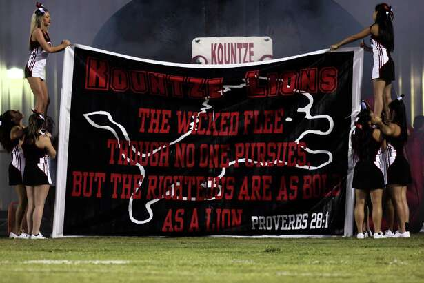 Kountze Lion's cheerleaders hold other members of their squads up to support a a larger banner at Lion's Stadium on Sept. 25.  Photo provided by Denzel Seale.