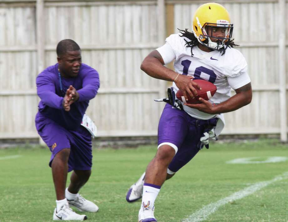 LSU's running back Terrence Magee runs through drills with coach Frank Wilson during practice on Monday, Aug. 4, 2014, in Batan Rouge, La. Wilson was named the new football coach at UTSA on Friday, Jan. 15, 2016, replacing Larry Coker. (AP Photo/The Advocate, April Buffington)   MAGS OUT; INTERNET OUT; NO SALES; TV OUT; NO FORNS; LOUISIANA BUSINESS INC. OUT (INCLUDING GREATER BATON ROUGE BUSINESS REPORT, 225, 10/12, INREGISTER, LBI CUSTOM); MANDATORY CREDIT Photo: April Buffington, AP / The Advocate