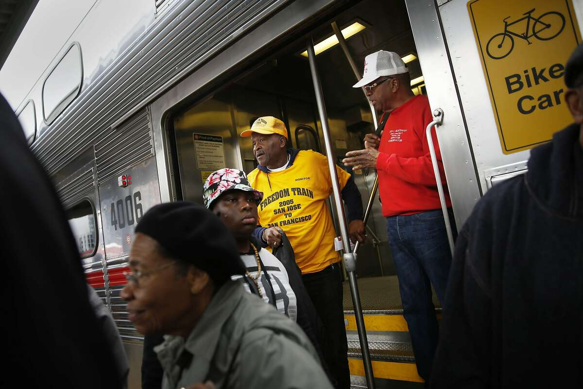Archie Moore (yellow shirt) ad Kenny Blackmon (red shirt), both of San Jose, disembark from the Freedom Train after arriving in San Francisco on Monday, January 19, 2014 in San Francisco, Calif.