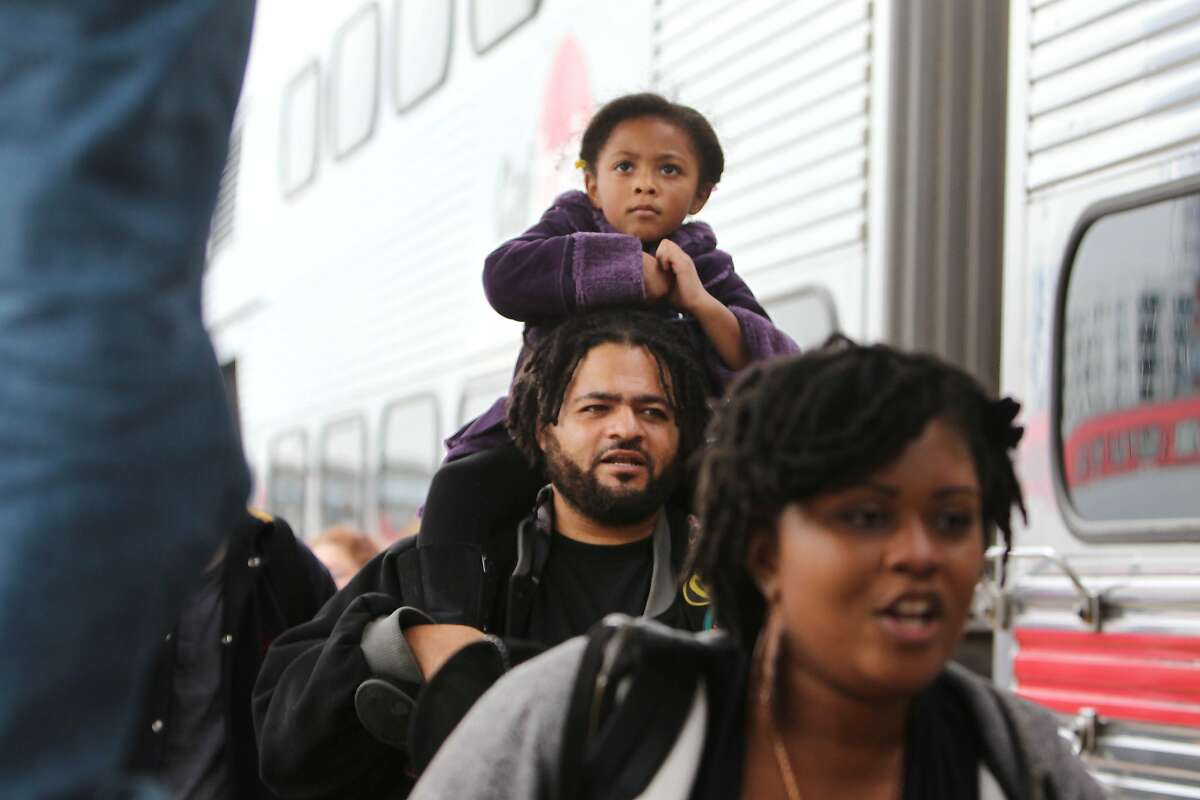 David Cuffy carries his daughter Anaiyah Cuffy, 4, both of Menlo Park, on his shoulders after disembarking from the Freedom Train at the Caltrain station on Monday, January 19, 2014 in San Francisco, Calif.