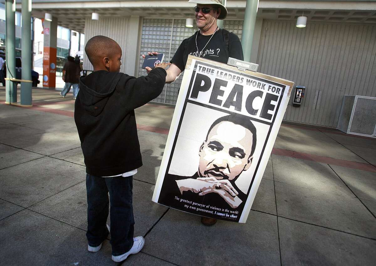 At the Fourth St. Caltrain station, Melvon Bellard, 6, who rode the Freedom Train from San Jose to San Francisco en route to the Martin Luther King Day celebration at the Bill Graham Civic Auditorium in San Francisco, Calif. on Monday, January 19, 2009 is given a postcard by Mike Carrick asking president Bush to end the war in Irag.