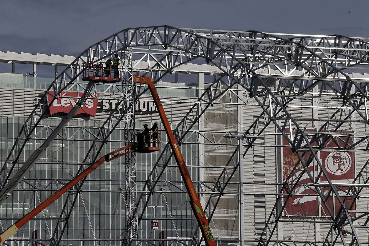 NFL crews erect a structure in the parking lots outside Levi's Stadium in preparation of Super Bowl 50 in Santa Clara, Calif., on Monday, January 11, 2016.
