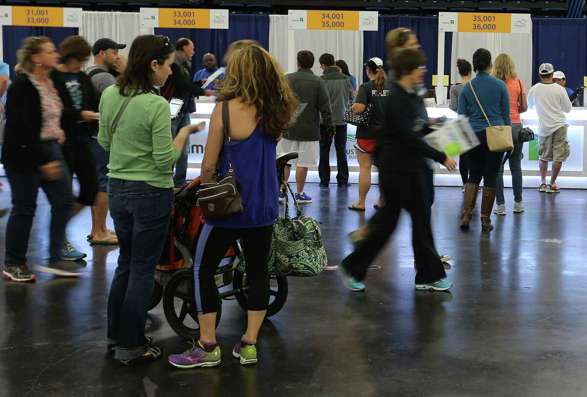 Runners pick up their numbers, swag and purchase items at the Memorial Hermann IRONMAN Sports Medicine Institute EXPO at George R. Brown Convention Center on Friday, Jan. 15, 2016, in Houston.